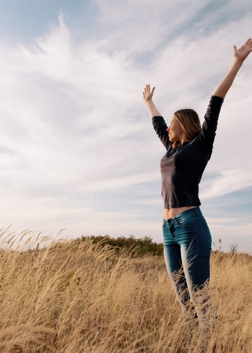 Young woman enjoying nature and freedom in a golden field under the blue sky
